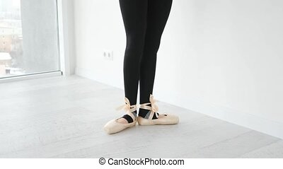 Ballerina dancing in beige pointe shoes. Beautiful legs ballet view