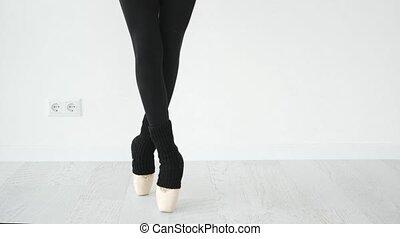 Ballerina legs in beige pointe shoes in white room. Girl dancing ballet in studio.