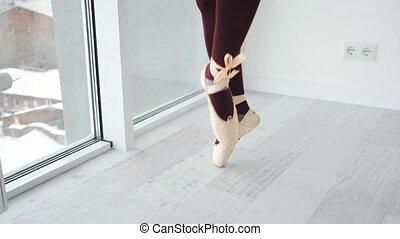 View of ballerina legs in beige pointe during morning perfomence. Elegant dance in white room