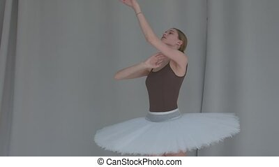 Ballerina on a light coloured background performs smooth movements with her hands. Graceful rehearsal of the part of the white swan in a spacious hall. Close up