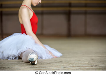Young beautiful ballerina dressing on tutu stretches before practice.