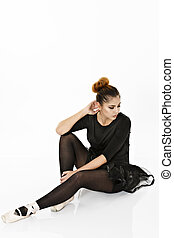 Ballerina posing on the floor isolated on a white background