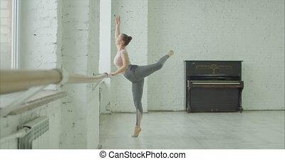 Ballerina practicing attitude in dance studio - Graceful...