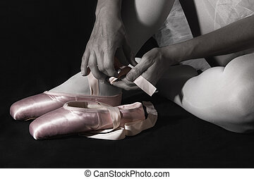Ballerina sit down on floor to put on slippers prepare  for perform artistic conversion