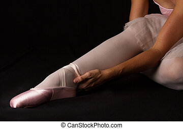 Ballerina sit down on floor to put on slippers with hands prepare for perform