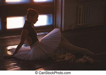 Ballerina sitting on floor in dark ballet class