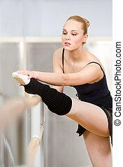 Ballerina stretches herself using barre