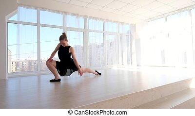 Ballerina stretching in ballet school