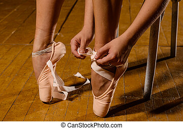 Ballerina tying pointe ballet shoes on stage