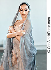 Ballerina with a perfect body and romantic fishnet dress is dancing in studio.