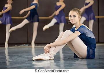 ballerina with smile sitting on the floor in a dance class dancers practicing on the background