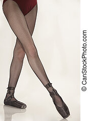 Close up of ballet dancer's legs in fishnet hose and pointe shoes
