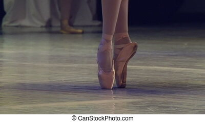 Feet in pointe dancing ballerinas on the stage. Slow Motion at a rate of 120 fps