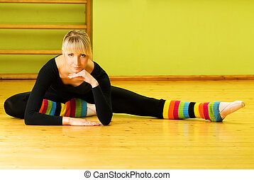 slim young ballet dancer doing stretching exercise sitting