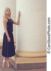 Ballet dancer in black dress and pointe