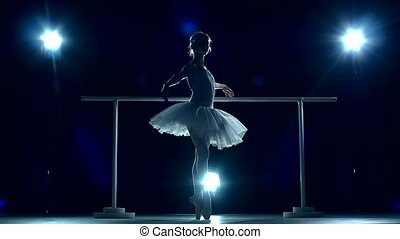 Ballet dancer in the classroom near barre. slow motion