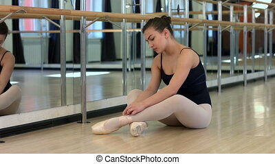 Ballet dancer is exercising - Tying Pointe shoes Slow motion