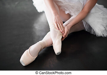 Ballet dancer legs in pointe shoes closeup