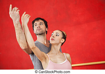 Ballet Dancer Performing With Trainer Against Red Wall