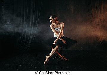 Ballet dancer sitting on black banquette