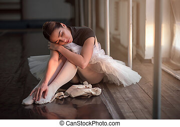 Ballet dancer sitting on the floor after rehearsal