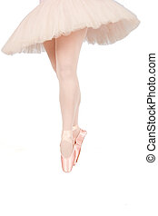 Ballet dancer standing on toes while dancing on white...