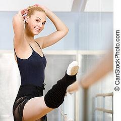 Ballet dancer stretches herself near barre