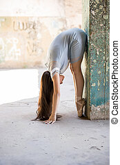 Profile view of a beautiful ballet dancer standing en pointe and stretching on a pillar in an abandoned building