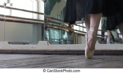 Ballet dancer warm-up her legs before training