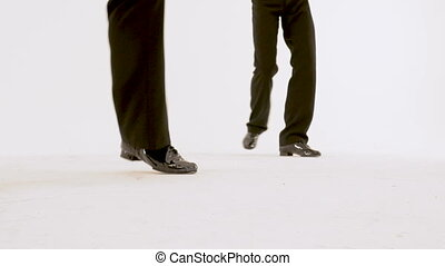 Ballet dancers' feet close-up Two men in black suits and red shirts dancing retro dance on a white background. They move beautifully and flexibly, perform synchronous exercises.