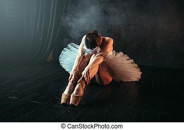 Ballet performer sits on floor, body flexibility