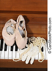 ballet shoes, lace glove and pearls on a piano