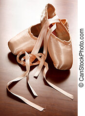 Ballet Shoes - Pink satin ballet shoes on dark floor in...