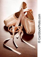 Pink satin ballet shoes on dark floor in slight soft focus
