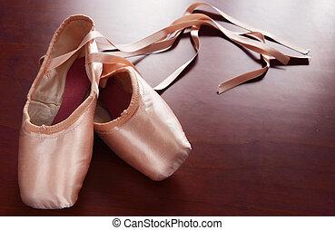 Ballet Shoes - Pink satin ballet shoes on dark floor