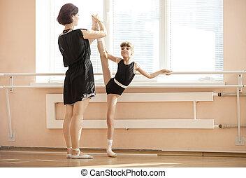 Ballet teacher adjusting leg position of young ballerinas at barre