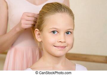 Ballet teacher fixing girls hairdo.