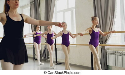 Ballet teacher is demonstrating leg and arm movements to her...