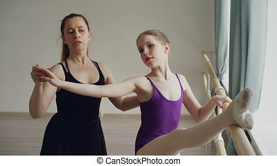Ballet teacher professional ballerina is teaching girl arm movements and bends at ballet barre during individual lesson in dancing school. Education and people concept.