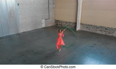 Ballet training indoors. Young woman ballerina dancing and...