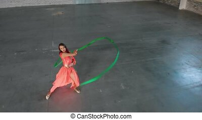 Ballet training indoors. Young woman ballerina performing...