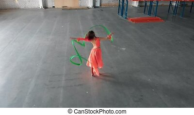Ballet training indoors. Young woman performing circus...