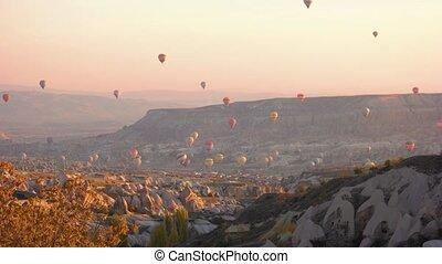 Balloon flight at Cappadocia, Turkey. Beautiful mountains landscape on sunset sky background. Amazing summer view.