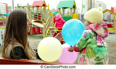 Balloon game - Little girl hiding behind colorful balloons...