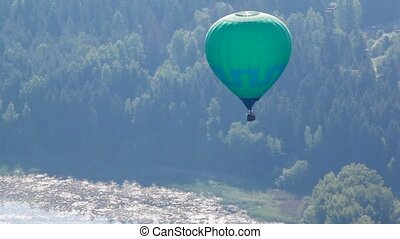 Balloon of green color flies far over the river and wood