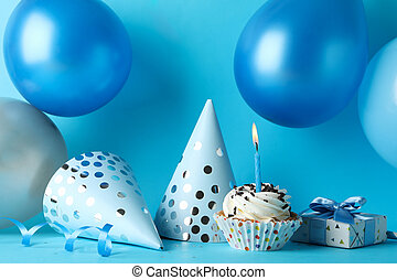 Balloons, birthday hats, cupcake and gift box on blue background, close up
