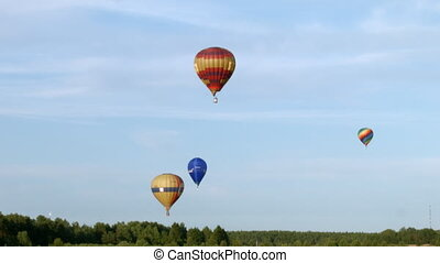 Balloons fly over the forest in evening