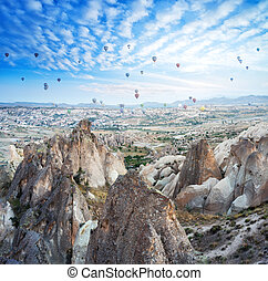 Balloons in the sky over the rocks of Cappadocia