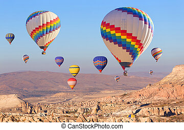 Balloons over Cappadocia. - Balloons flying over rock ...