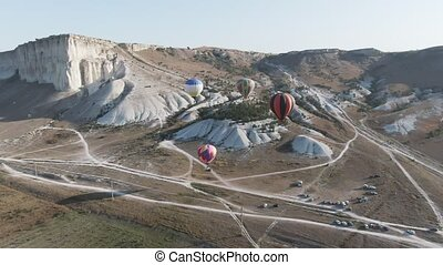 Balloons soar over the Valley amid protruding mountain ...